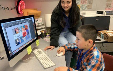 Yearbook editor junior Mariel Joven shows elementary schooler Dylan Hernandez-Perez a yearbook spread.