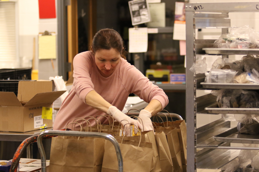 A volunteer assembles a meal bag. Assembly of bags took place in the HHS cafeteria and included snacks like raisins.