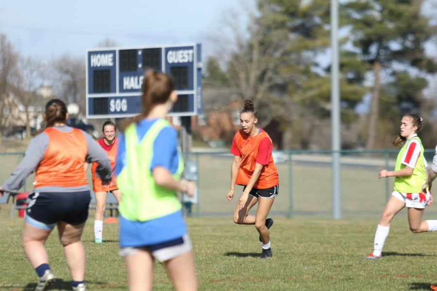 Sophomore Olivia King kicks a ball during a drill at the girls practice.