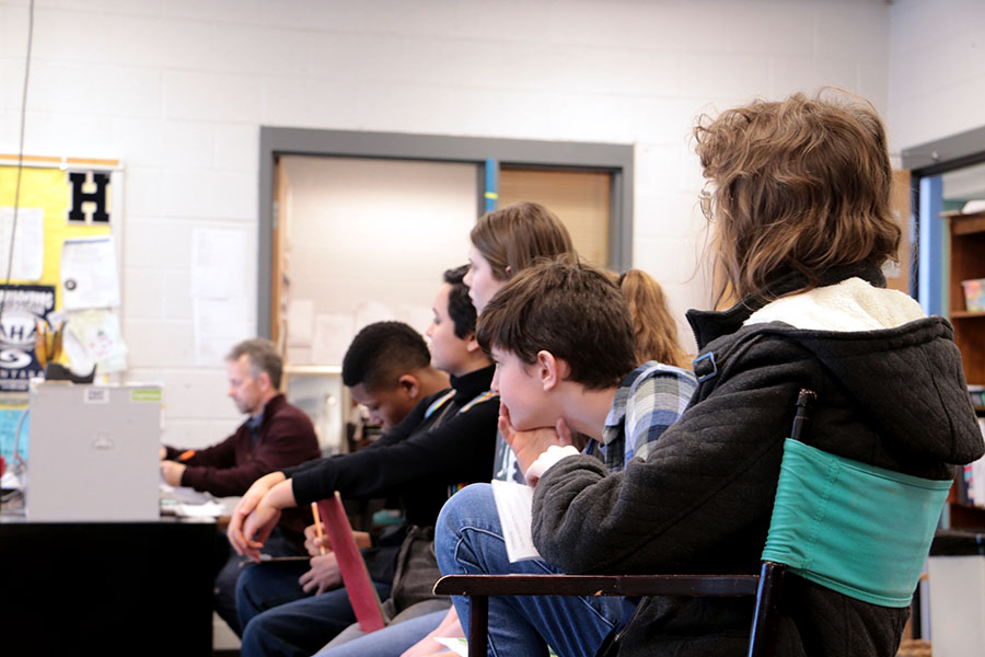 Students listen to director Aili Huber as they prepare for play auditions.