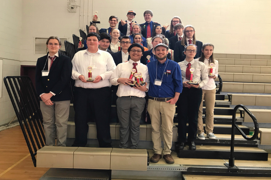 The HHS TSA chapter stands together with one of their leaders, Seth Shantz,  and THMS TSA members. The chapter holds up awards they won through the competition.