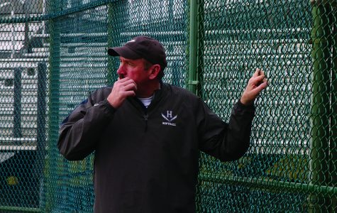 Head coach Scott Sheets stands on the fence and looks out as his team prior to the start of practice.