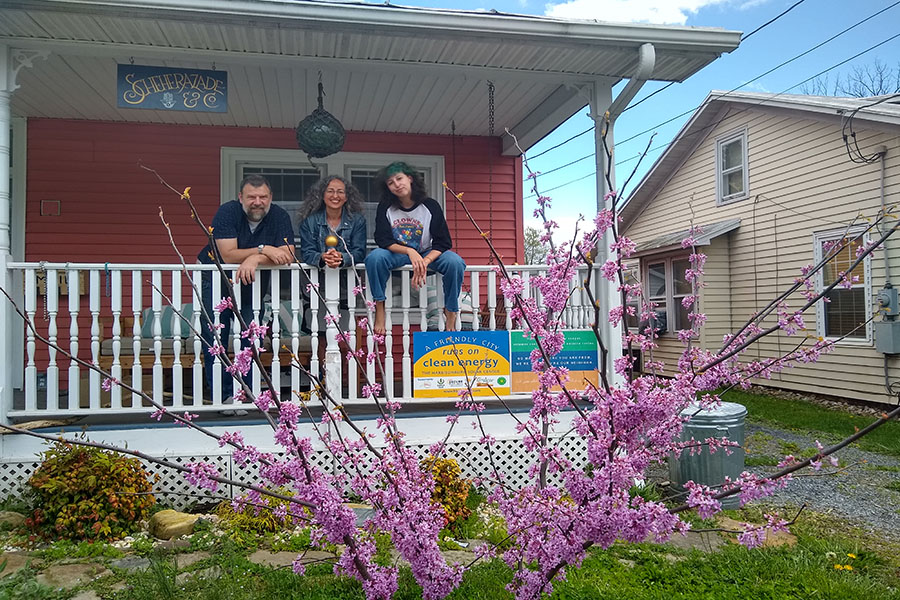 (From left to right) Keith Miller, Sofia Samatar and junior Isabel Samatar stand on their porch.