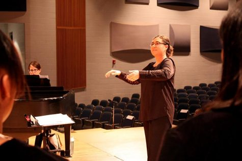 Choir teacher Bethany Houff conducts her students during a concert.