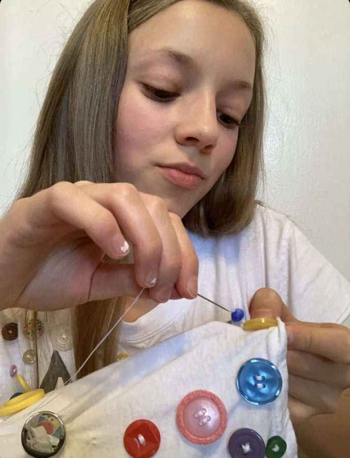 Corso sews buttons onto some fabric to add to her many miscellaneous products on her instagram page,