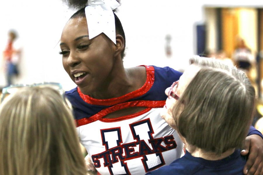 Senior Dorothy Yates after a successful competition cheer routine last year, embracing her mother and late grandmother.