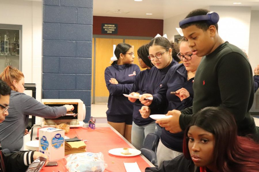 Students get in a line to get their s'mores made by SCA advisor Danae Delozier during a basketball game last year.