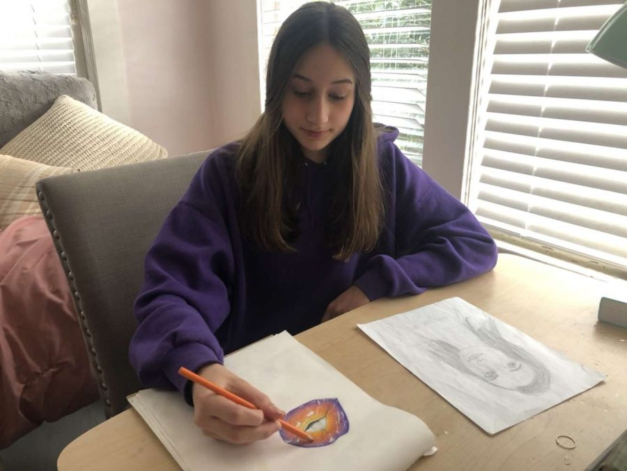 Freshman Anna Campillo works on a drawing of lips in her room.