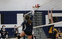 Freshman Lucy Ludwig reaches up to bump the ball over the net.