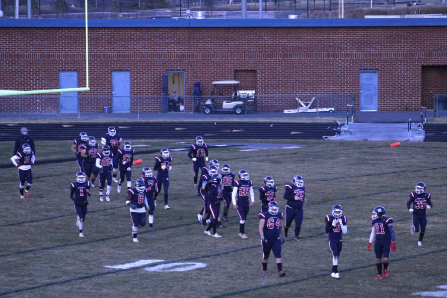 The HHS varsity football team enters the football field after the twelve minute halftime, ready to do their best on the field before the game ends.