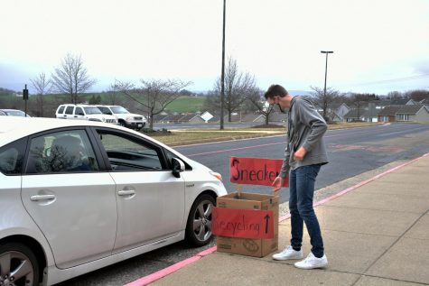 Eighth grader Lucas Swartz assists community members in placing their sneakers into the recycling box.
