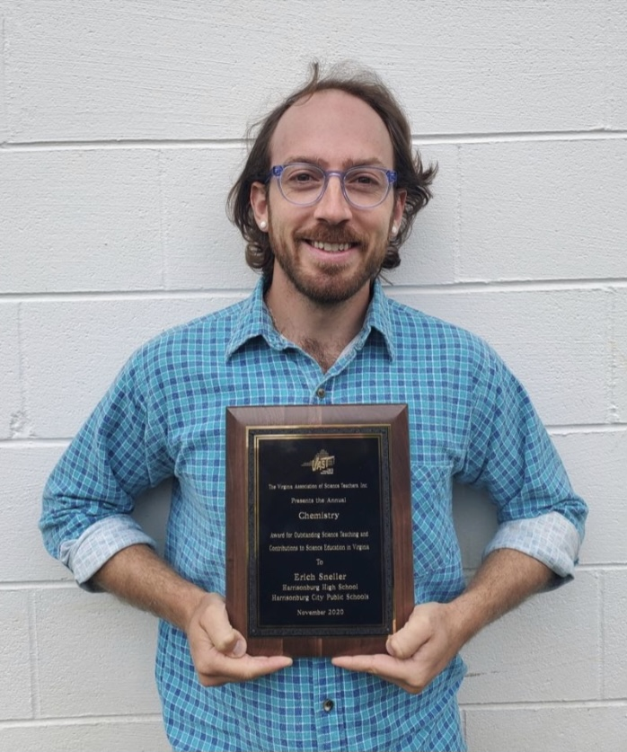 HHS Chemistry teacher Erich Sneller standing with the plaque he received from the Virginia Association of Science Teachers for the Recognition in Science Education Award. This is the first year Sneller won the award.