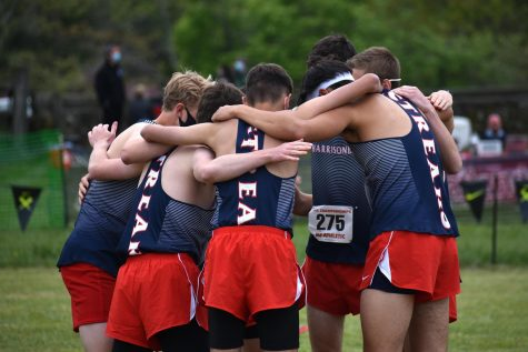 The boys cross country team huddles before their race. The boys team placed second at the regional meet, qualifying them as a team for the state championship.