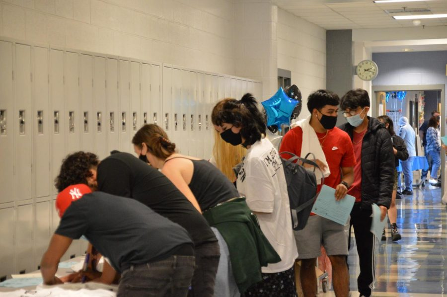 Seniors line up to write on their decision day t-shirts.