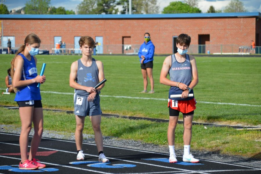 Sophomore Liam Wightman stands at the starting line holding a baton with a Spotswood and Rockbridge runner.