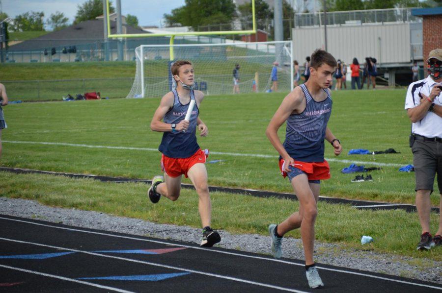 Freshman Nathaniel Bunn runs to pass the baton to freshman Matthew Rush.