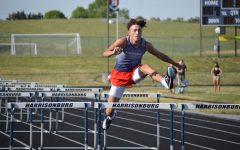 Sophomore Jadon Burgess jumps over a hurdle.