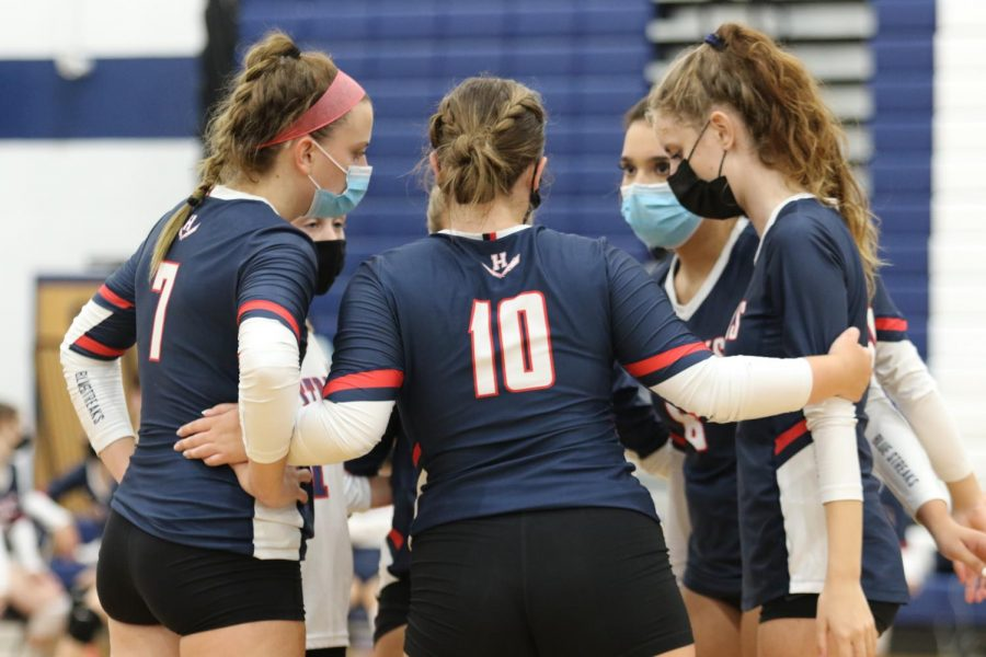 Members of the girls varsity volleyball team huddle up to discuss before they go back into the game.