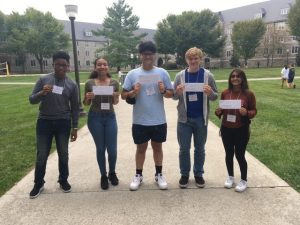 (Left to right) Seniors Jory James, Haile Madden, Jafar Mansoor, Adam Osinkosky and Aroob Ahmed hold up their envelopes prior to finding out their admissions decision after the conclusion of fall visitation weekend at Virginia Tech.