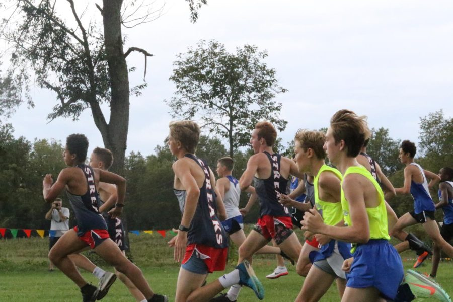 The JV Boys Cross Country team sprints at the start of the 5k race.
