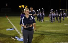 Principal Melissa Hensley  presents homecoming crowns to elected royalty during halftime of the varsity football game.