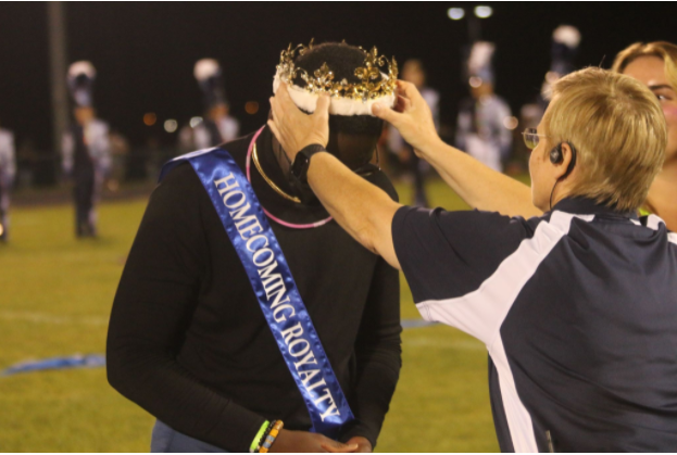 Senior Kofi Darko gets crowned by Dr. Melissa Hensley for homecoming royalty at halftime of the homecoming game.