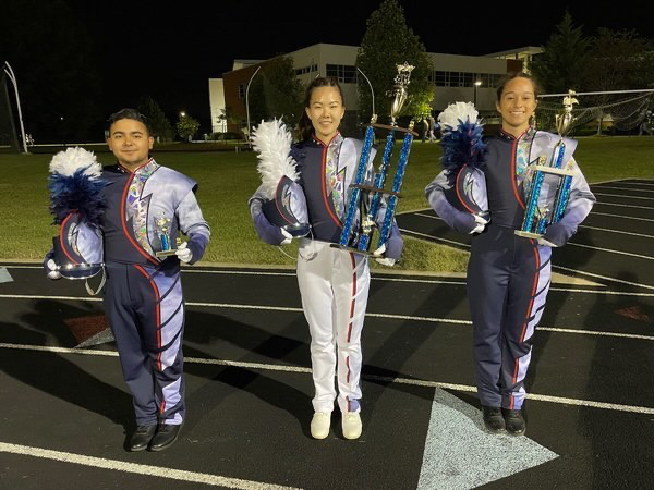 Seniors and assistant drum majors Mikey Paniagua, Jeslyn Liu and AJ Moats hold their trophies from the Star City Classic competition.